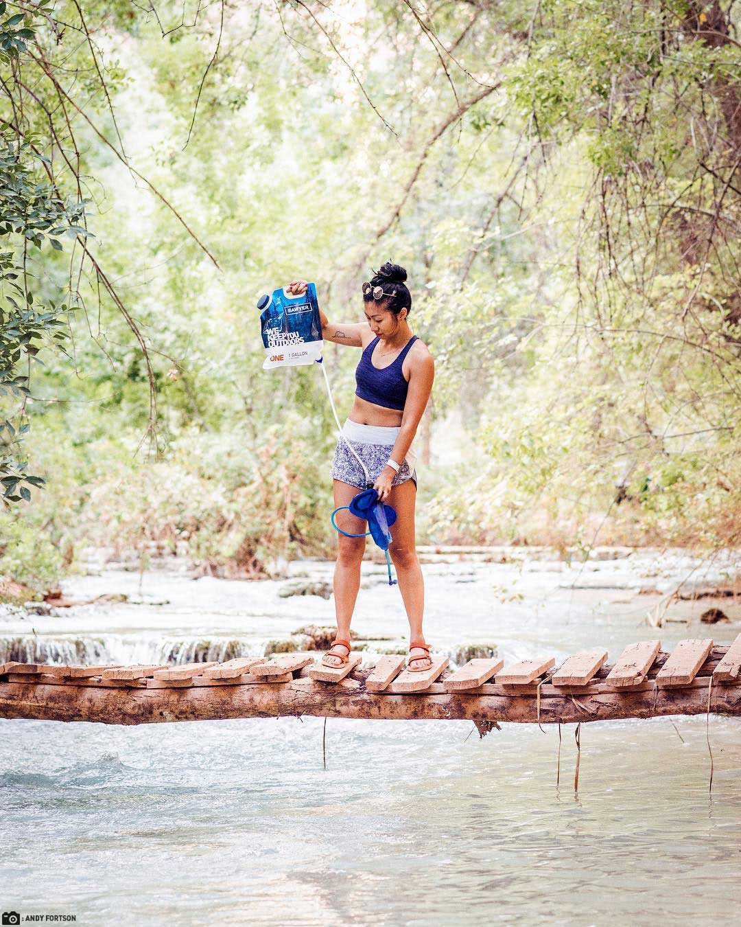 A Woman Uses a Sawyer Gravity Filtration System to Fill her Hydration Pack