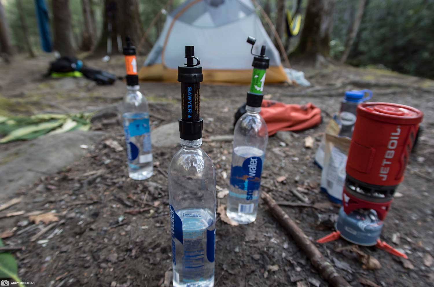 A Campsite Photo with Sawyer MINI Water Filters on Smart Water Bottles in Front of a Tent