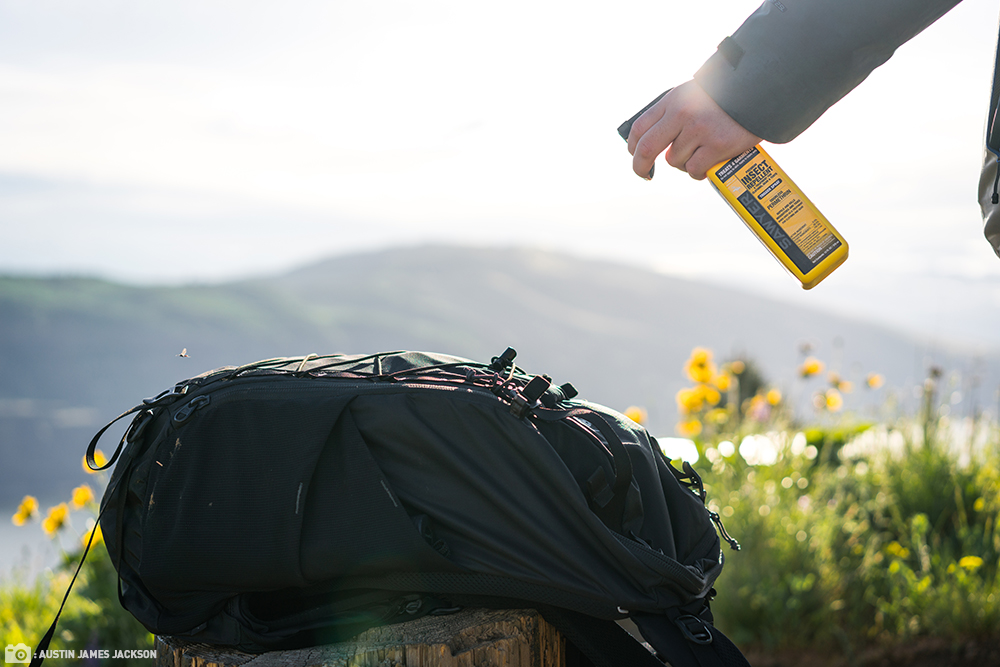 A hiker refills their Sawyer water filter in a river.