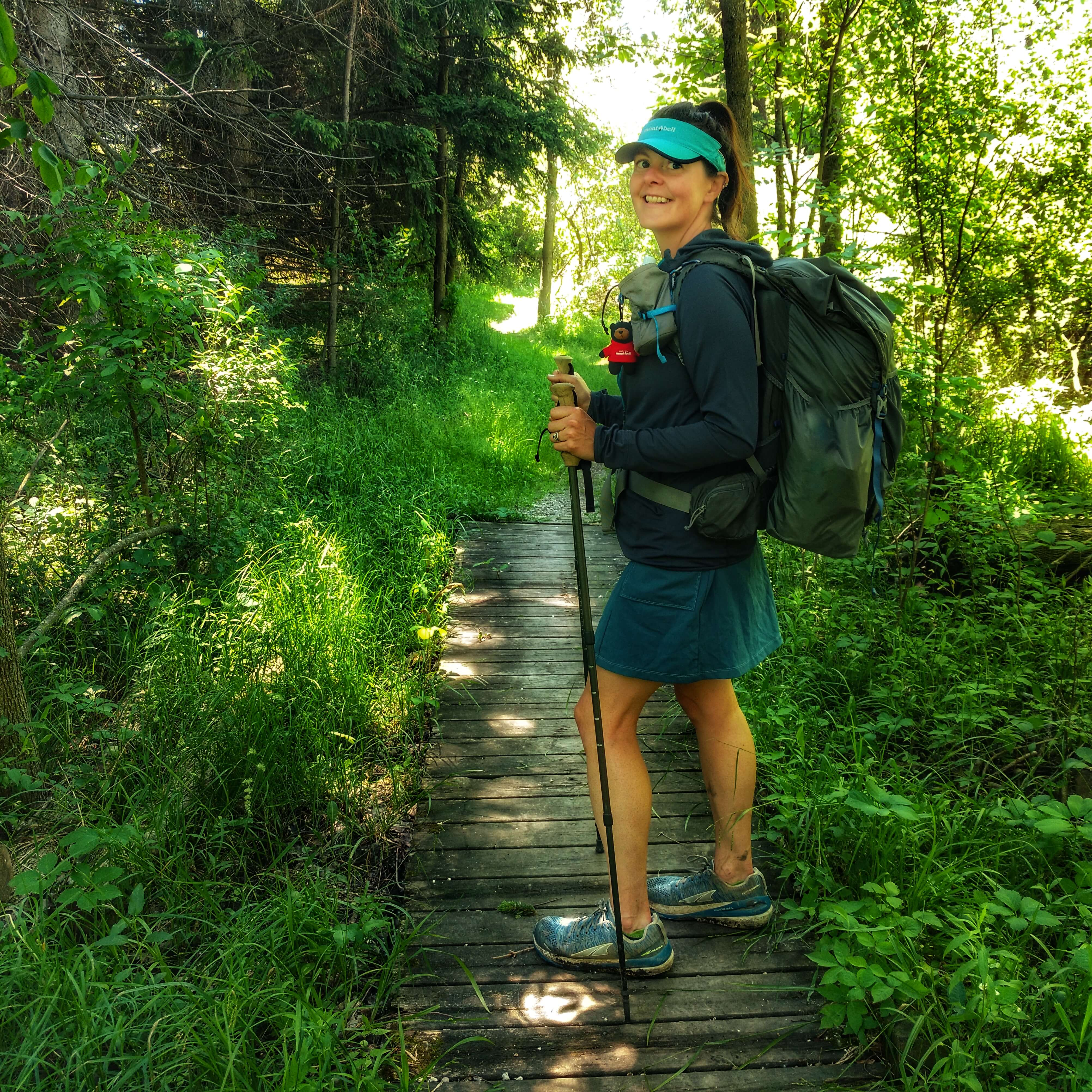 A picture of a woman hiking in green forest