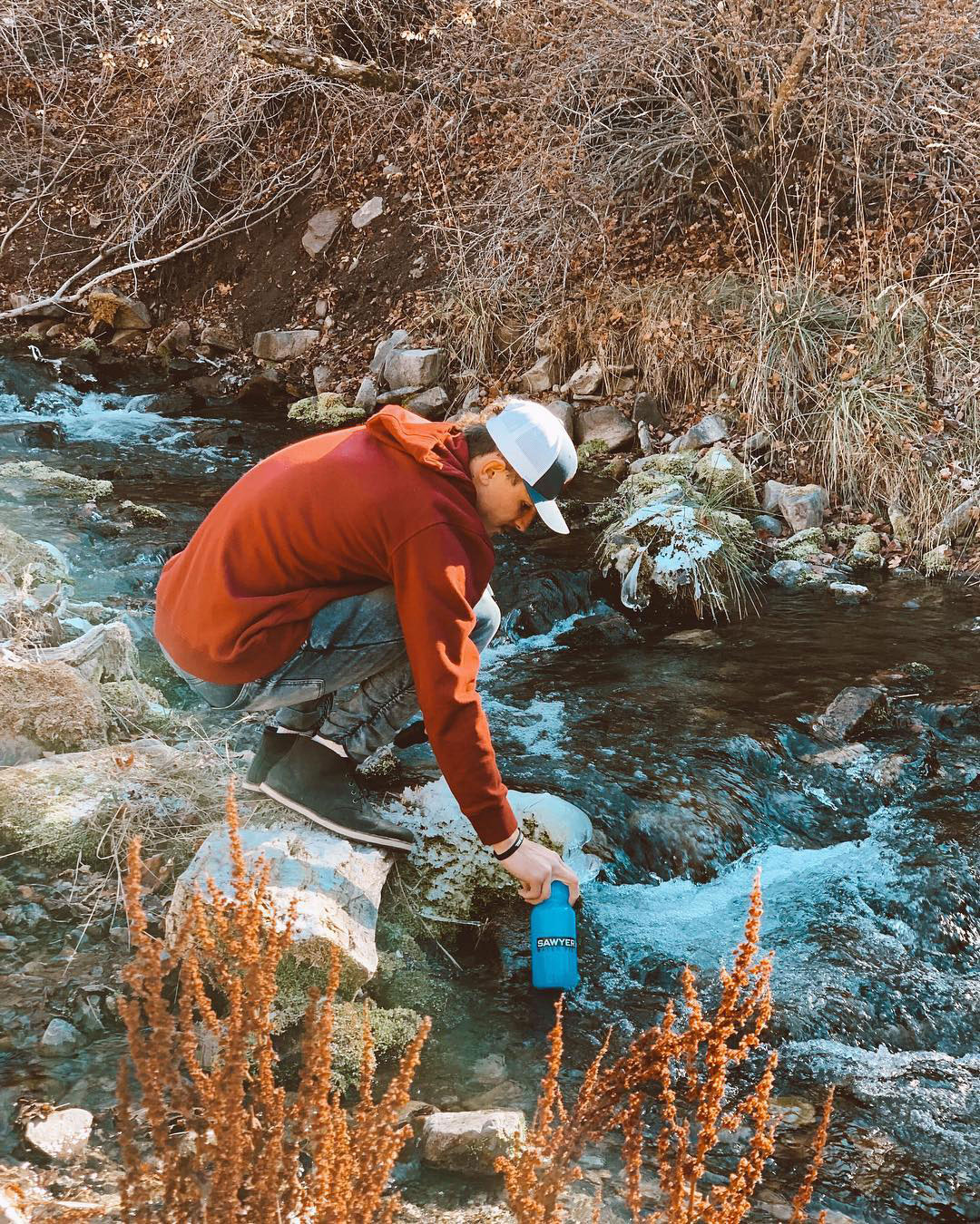 Gentleman Fills his Sawyer Personal Water Filtration Bottle in a Stream