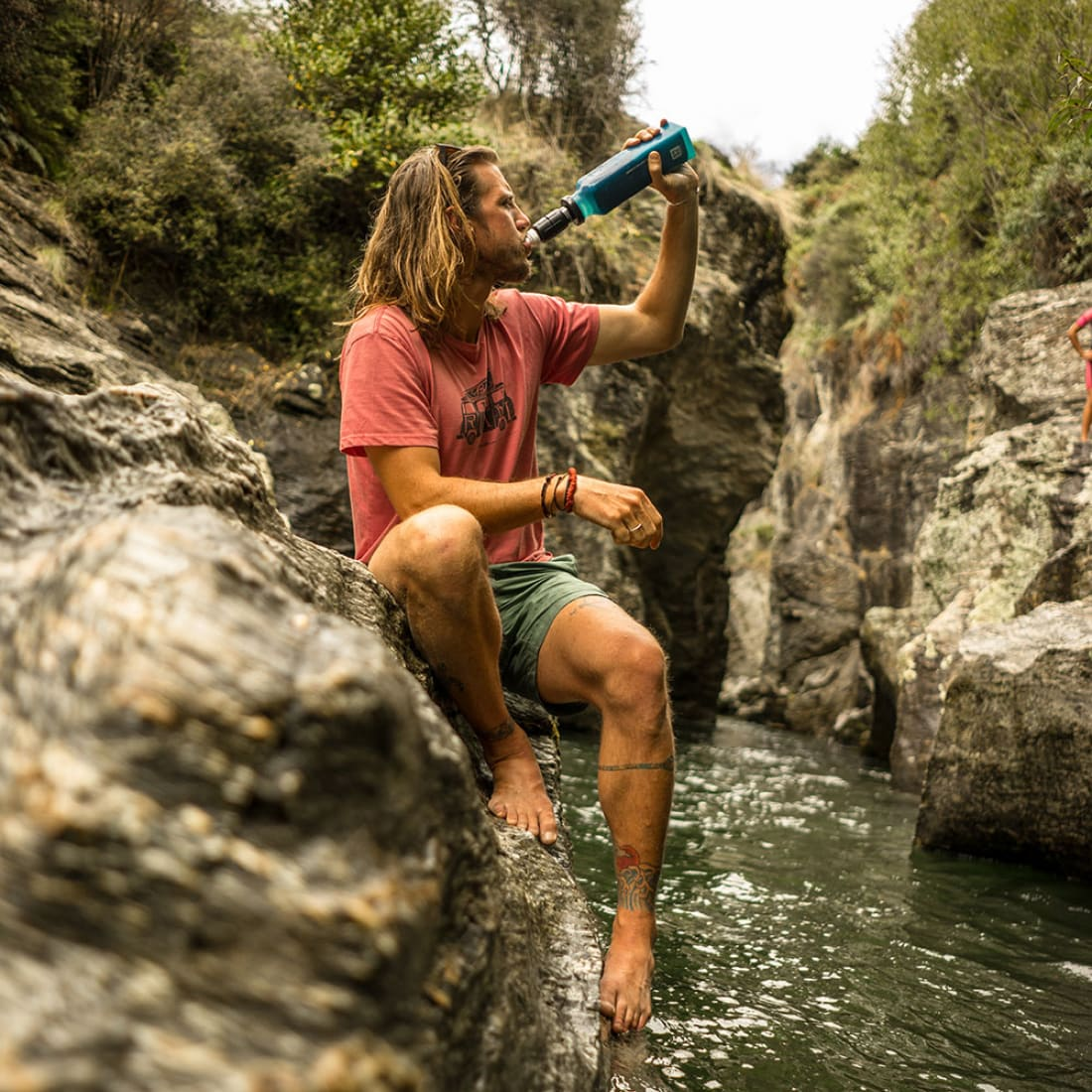 A hiker drinks from an S1 filter sitting next to a creek.