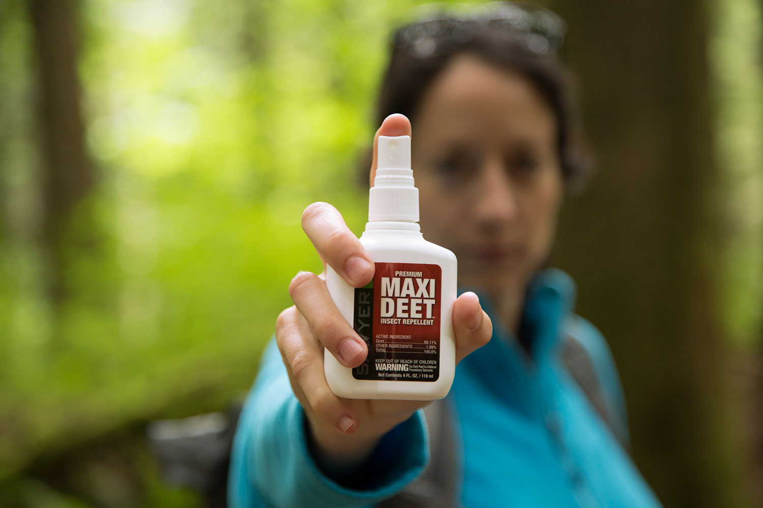 A Woman Holding Sawyer MAXI DEET Insect Repellent Spray Towards the Camera in the Woods
