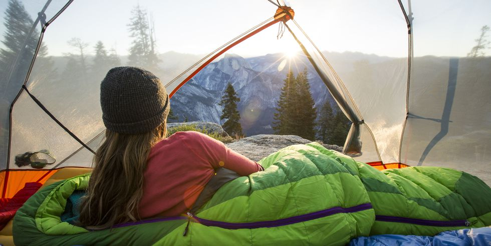 Popular Mechanics woman-watching-sunrise-from-a-tent-high-res-stock-photography-531284673-1558125902
