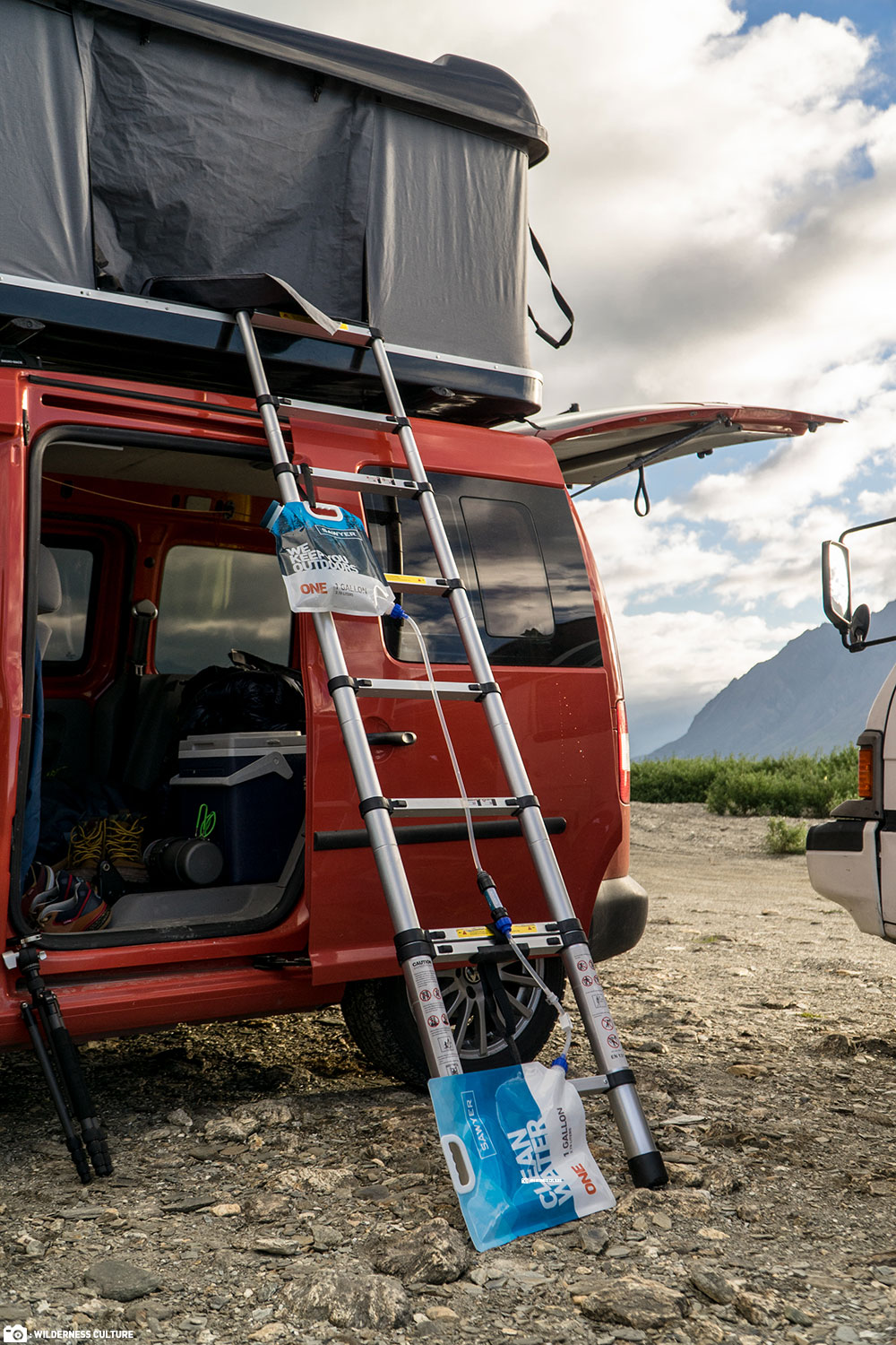 A Dual Bladder Sawyer Gravity Water Filtration System on the Ladder of an Adventure Van