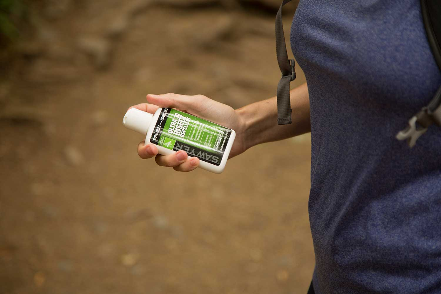 A Woman Holding a Bottle of Sawyer Ultra30 Insect Repellent Lotion in the Woods