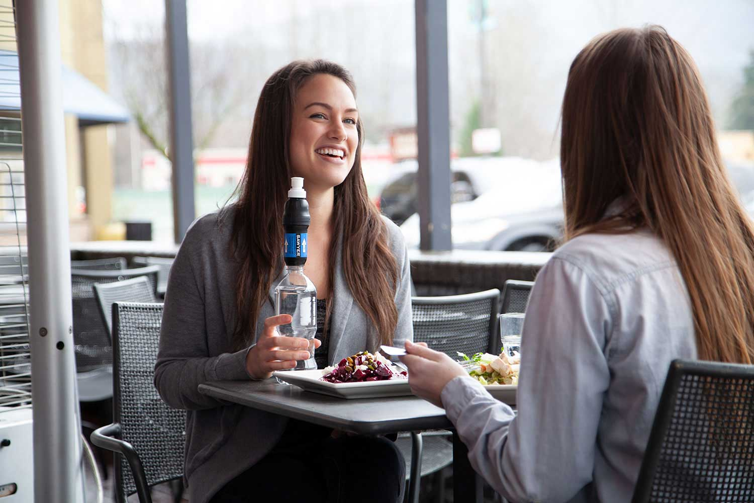 Two Women Use Sawyer Water Filters on Water Bottles While Traveling and Eating at a Restaurant