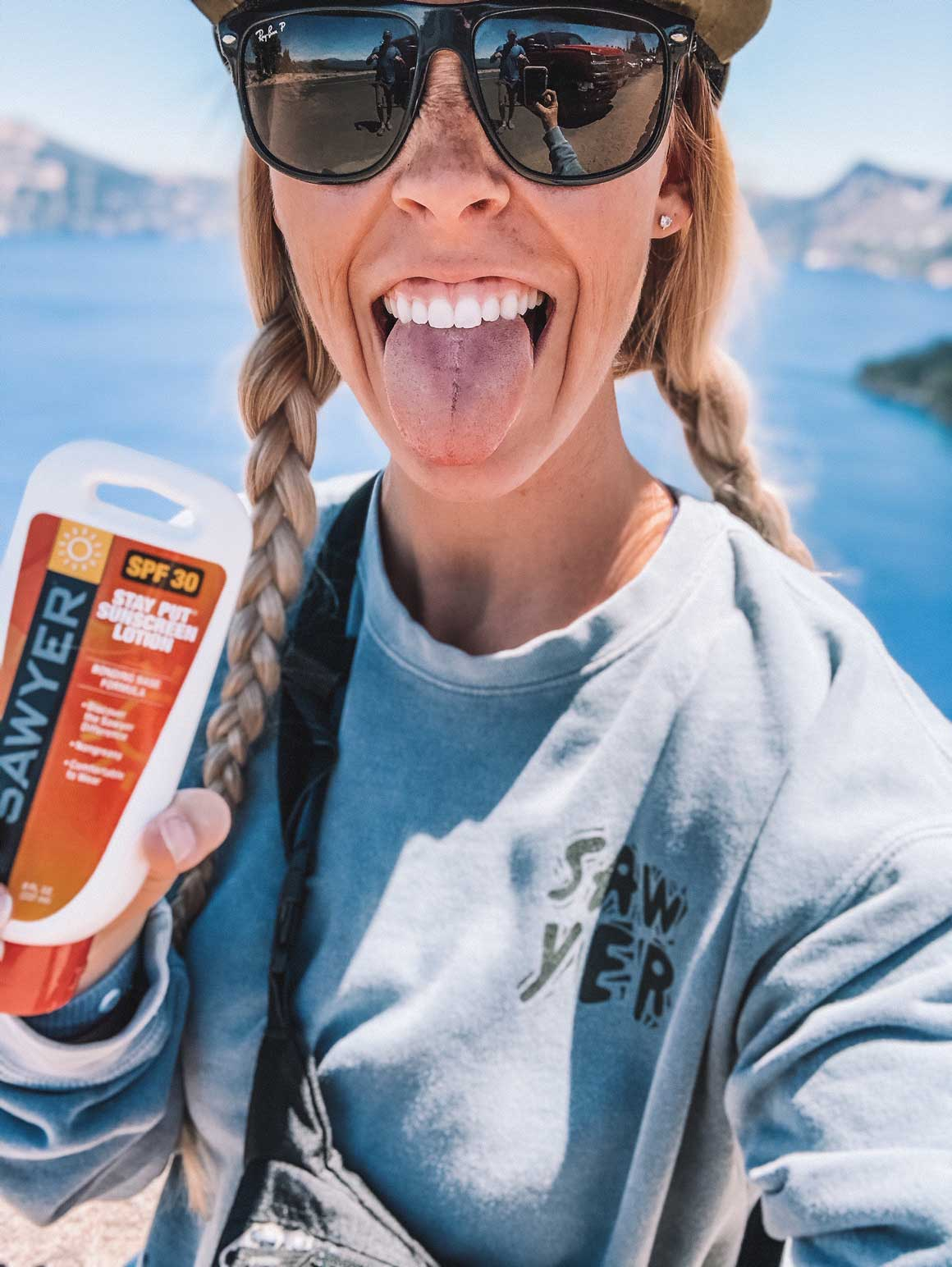 A Woman Excitedly Holding a Bottle of Sawyer Stay Put Sunscreen in Front of the Water