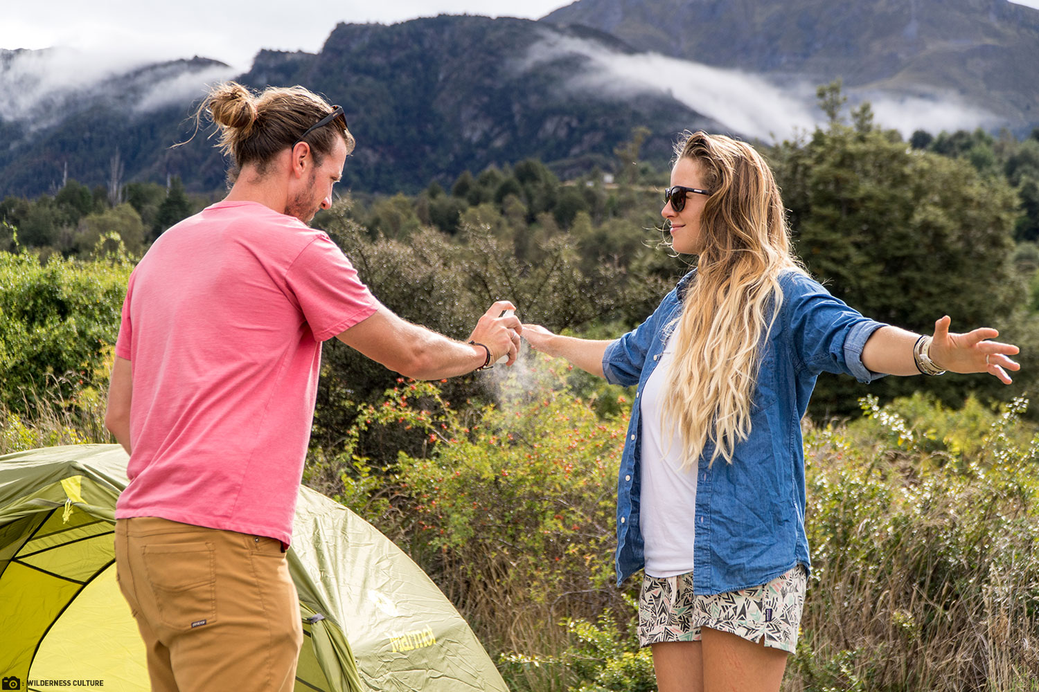 A Gentleman Applies Sawyer MAXI DEET Insect Repellent Spray to His Camping Partner