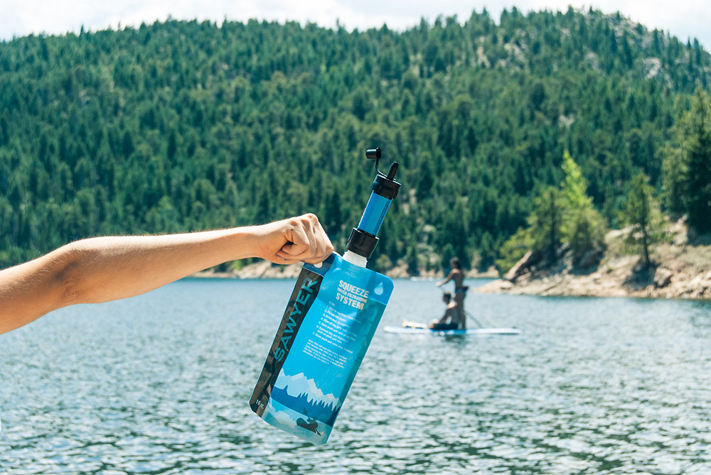 A Sawyer MINI Water Filter out on a Lake While Paddleboarding