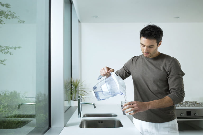 man-in-kitchen-pouring-glass-of-filtered-water-768x768