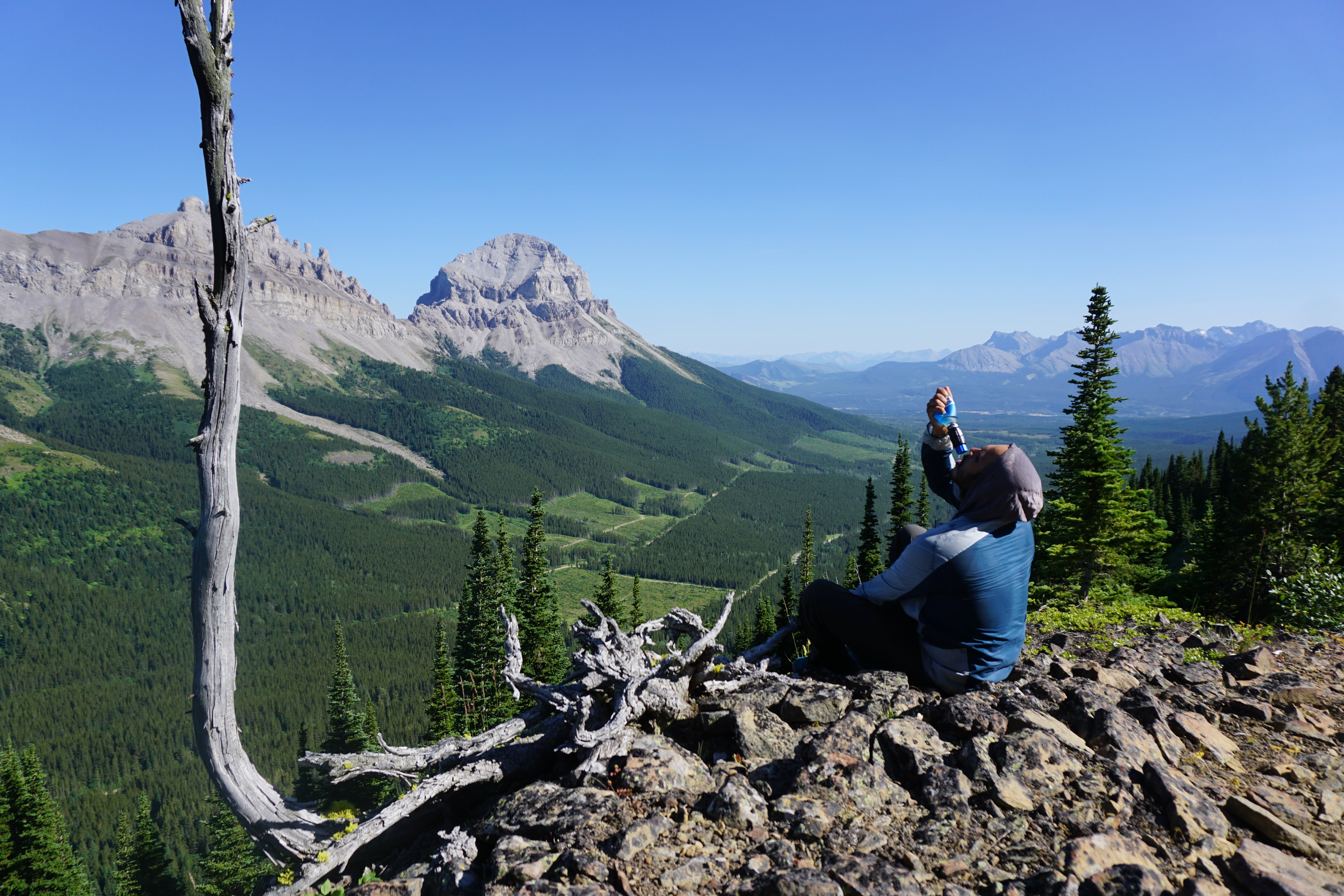 Hiker overlooks a lookout point and drinks from Sawyer filter