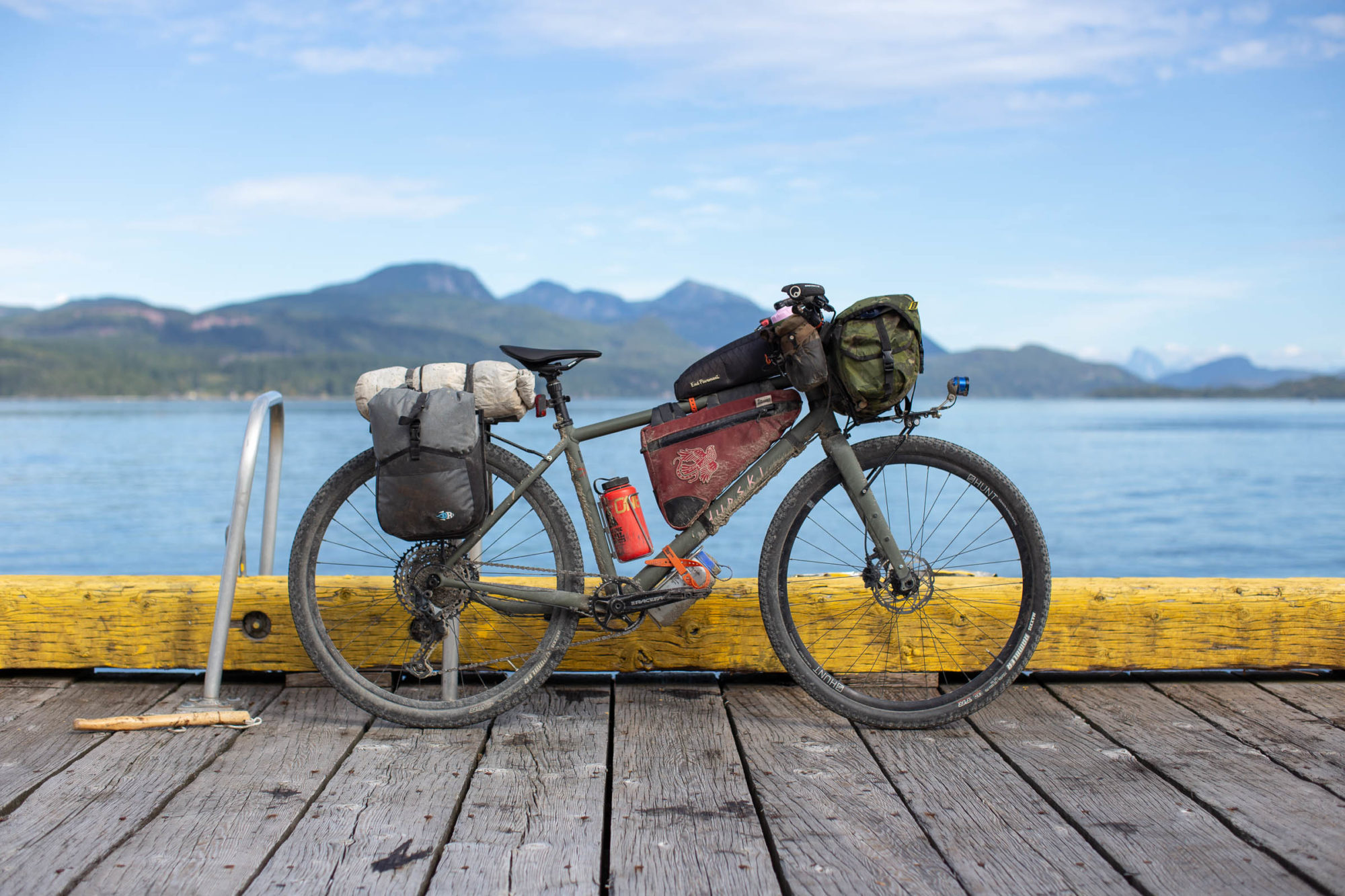 Bikepacking bike on a wooden doc in front of a lake.